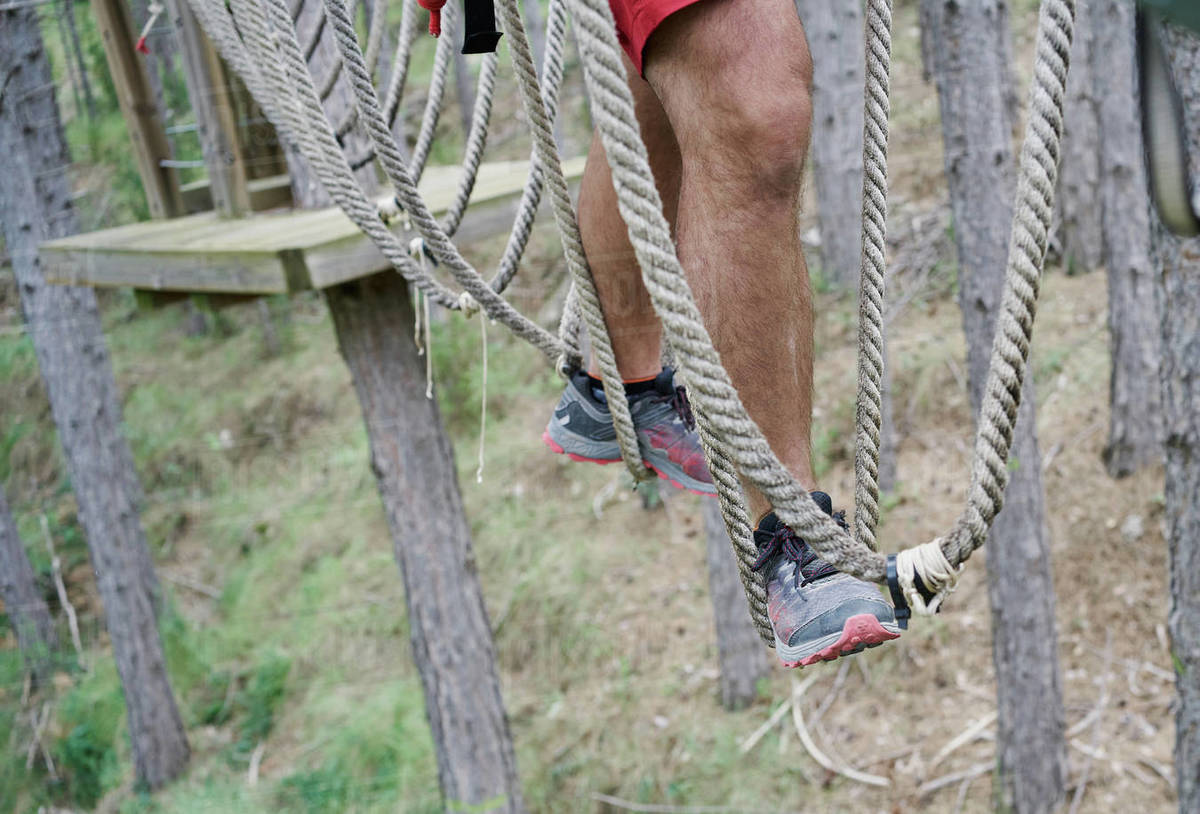 Unrecognizable male in sneakers walking on rope course in adventure park in forest Royalty-free stock photo