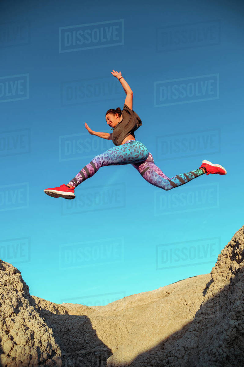 From below full body of active energetic female in sportswear leaping high above sandy slope of desert terrain against blue cloudless sky Royalty-free stock photo