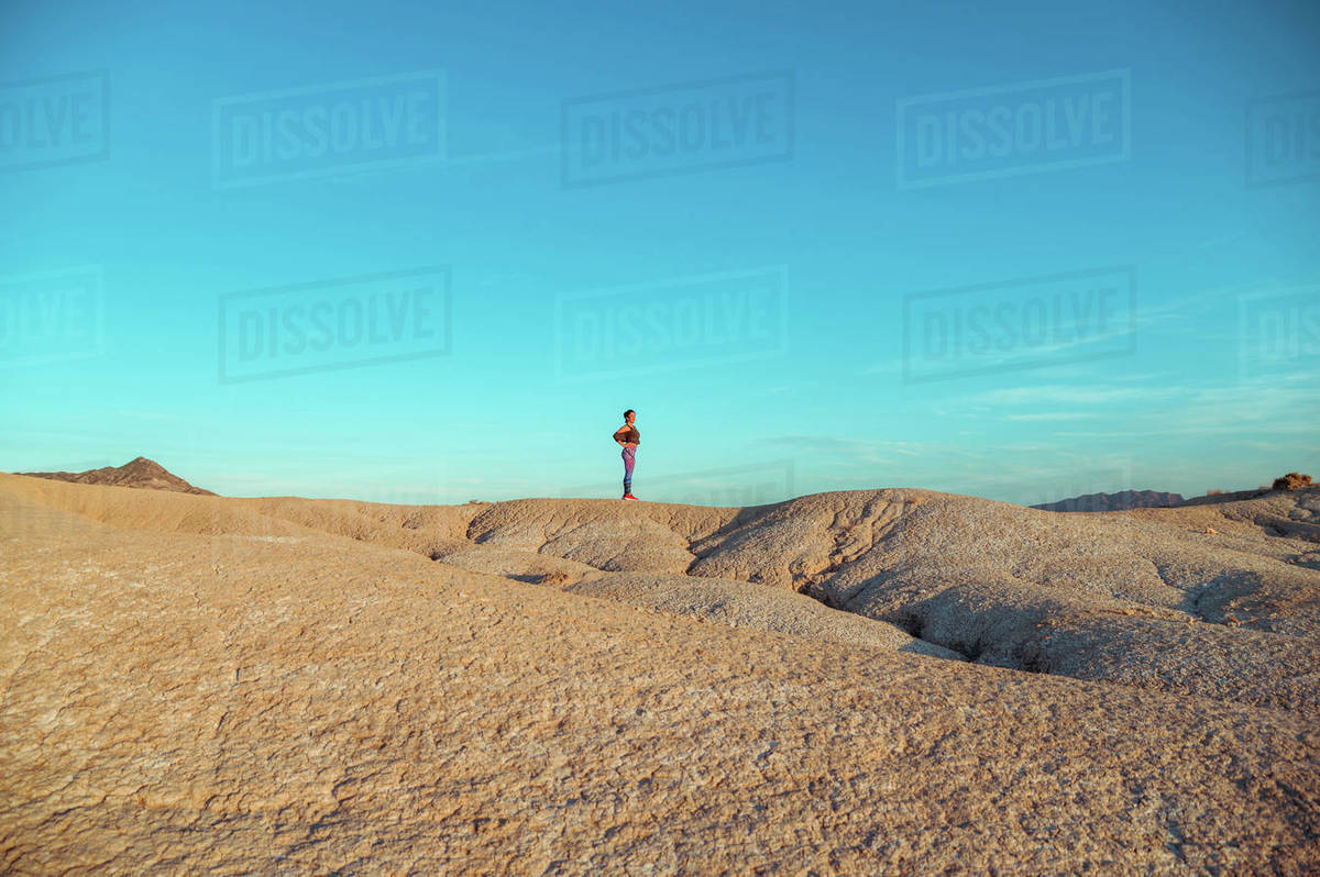 Side view of female in sportswear standing on rocky hill among desert badlands against blue cloudy sky Royalty-free stock photo