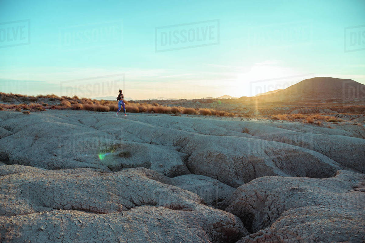 Back view of unrecognizable active female athlete in sportswear running and jumping over rocky slope of rough desert hilly terrain under blue sky Royalty-free stock photo