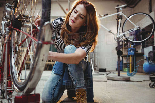 Woman looking at a bicycle in a workshop Royalty-free stock photo