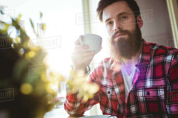 Hipster with coffee cup sitting by window at cafe Royalty-free stock photo