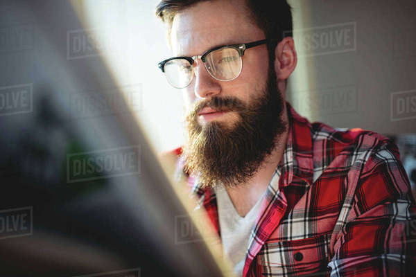 Young hipster reading newspaper at coffee shop Royalty-free stock photo