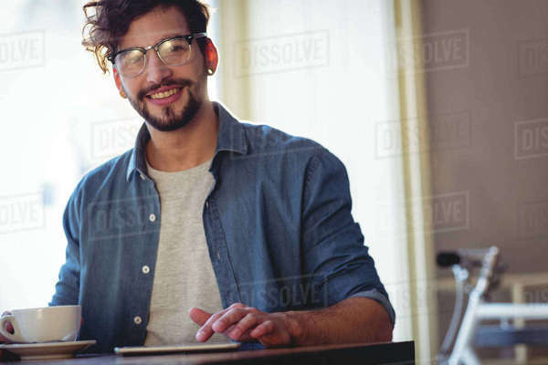 Portrait of happy young handsome man with cellphone and coffee at cafe Royalty-free stock photo