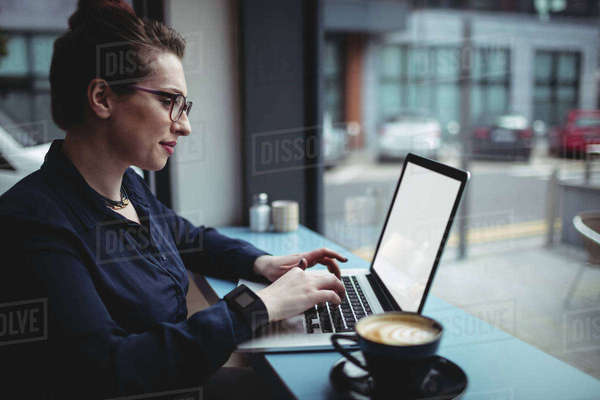 Young businesswoman using laptop in cafe Royalty-free stock photo