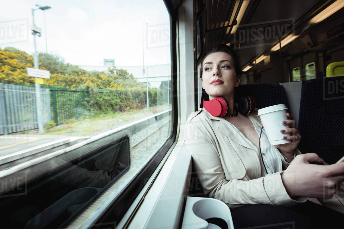 Beautiful woman sitting by window in train - Stock Photo - Dissolve