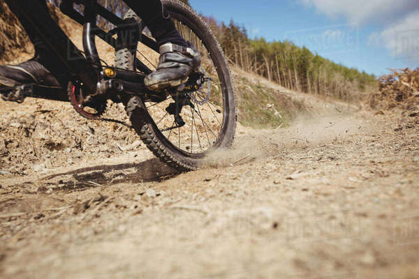 Low section of biker riding on dirt road at mountain against sky Royalty-free stock photo