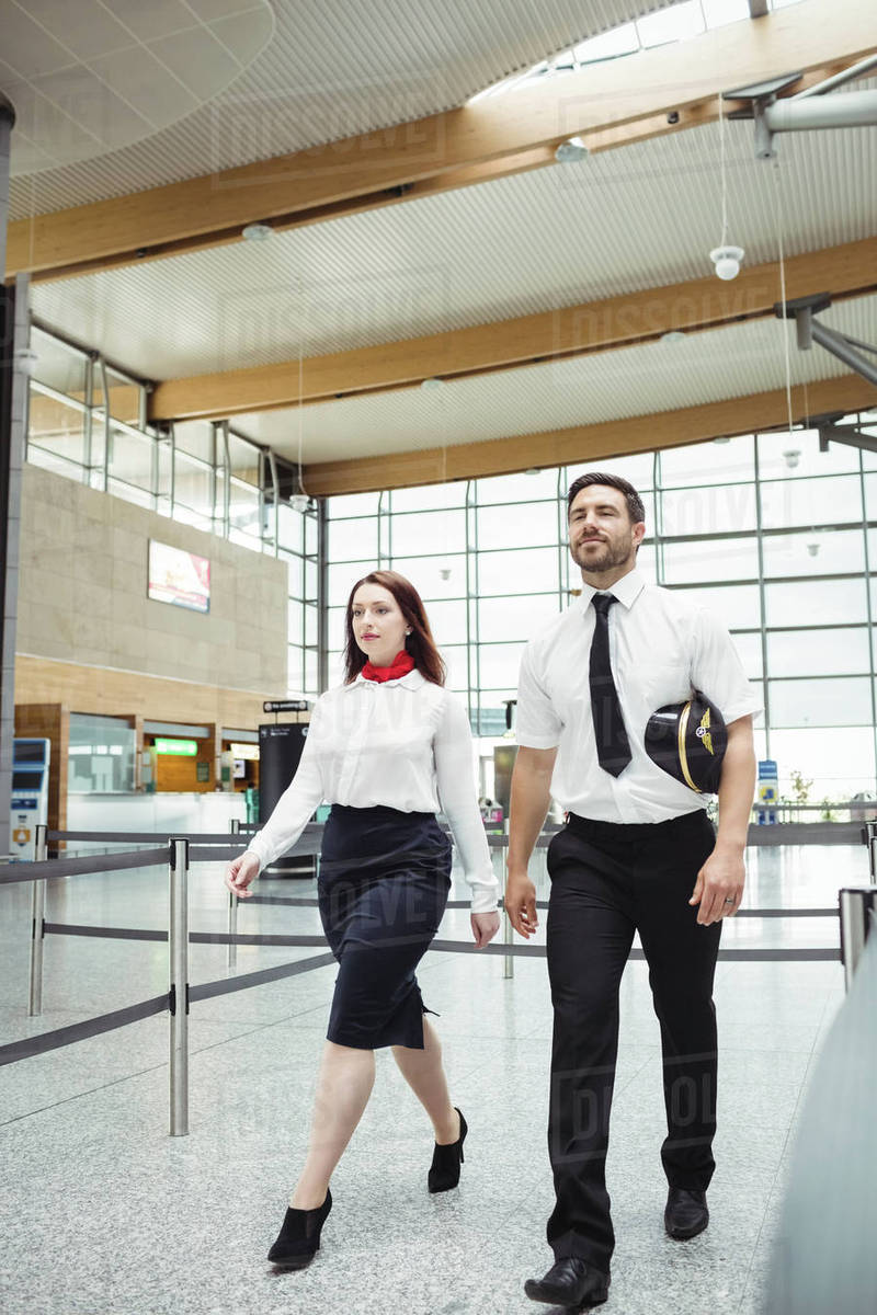 Pilot and flight attendant walking at the airport stock photo