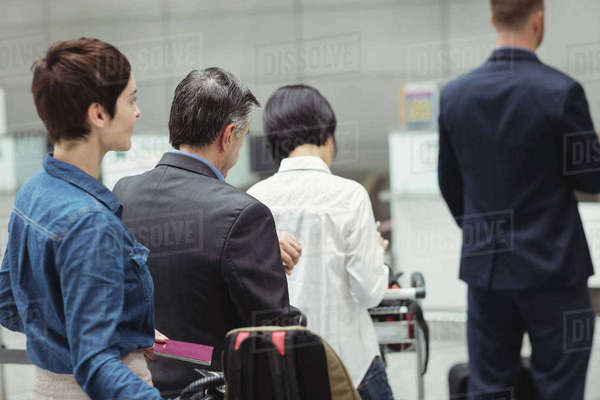 Passengers waiting in queue at a check-in counter with luggage inside the airport terminal  Royalty-free stock photo