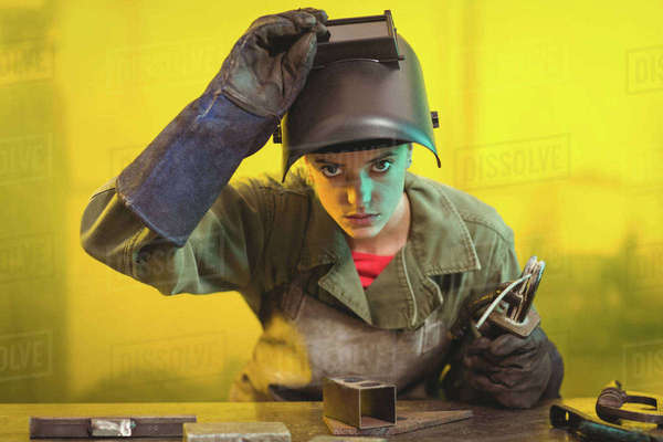 Female welder examining a piece of metal in workshop Royalty-free stock photo