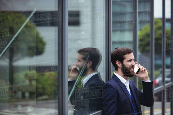 Businessman talking on mobile phone outside office Royalty-free stock photo