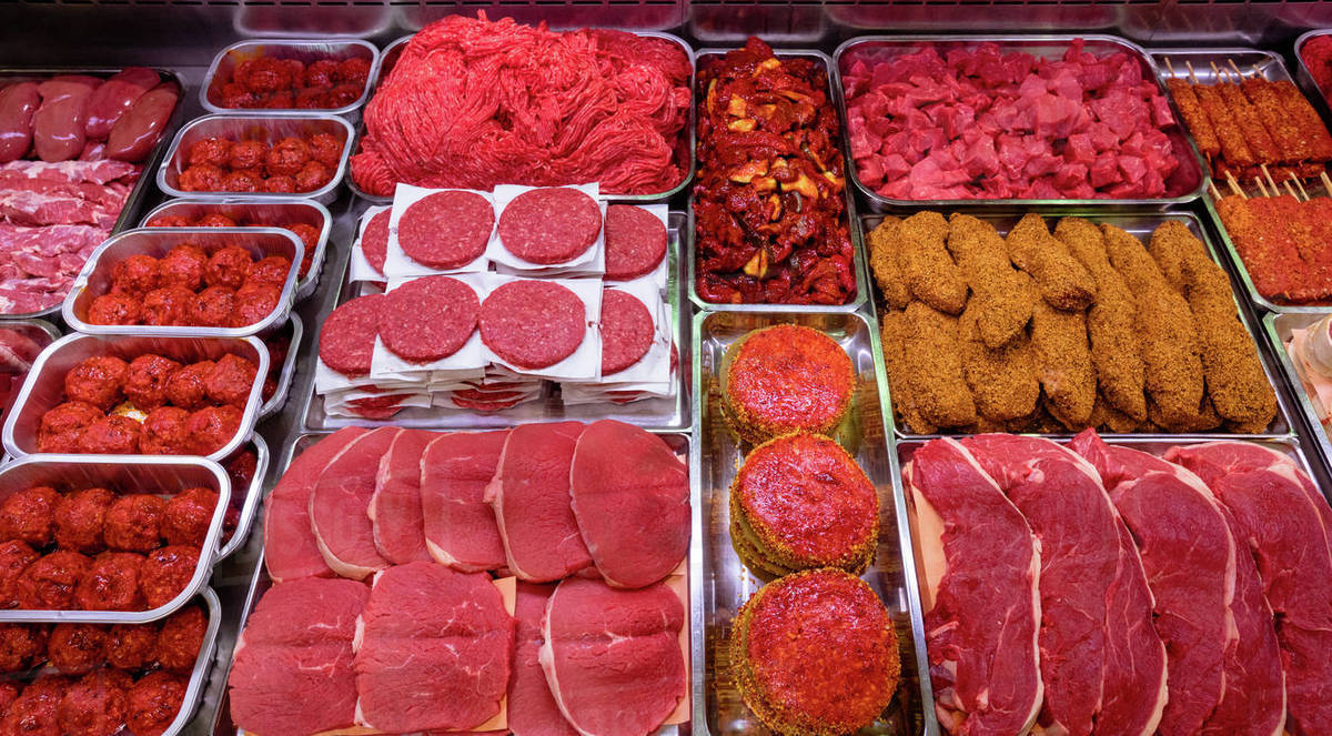 Variety Of Marinated Meat At Display Counter In Butchers Shop Stock Photo