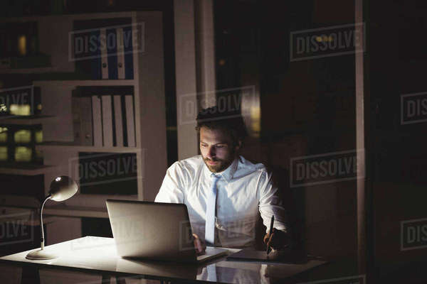 Businessman drawing on graphic tablet at night in the office Royalty-free stock photo
