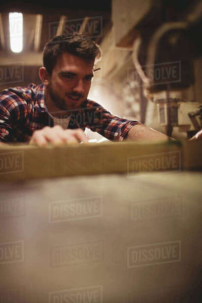 Carpenter working on his craft in a dusty workshop Royalty-free stock photo