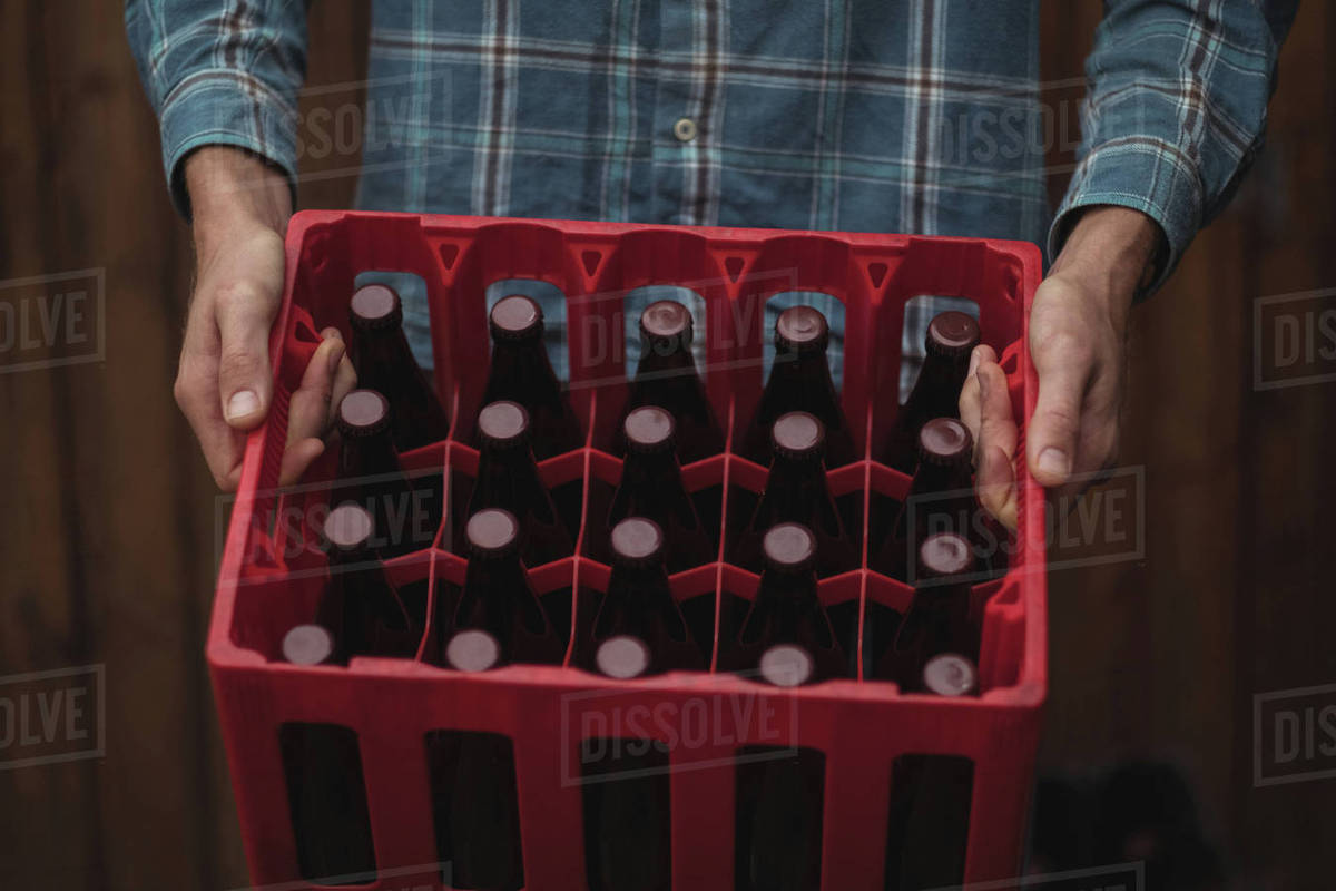 Close-up of man carrying homemade beer bottles in a crate