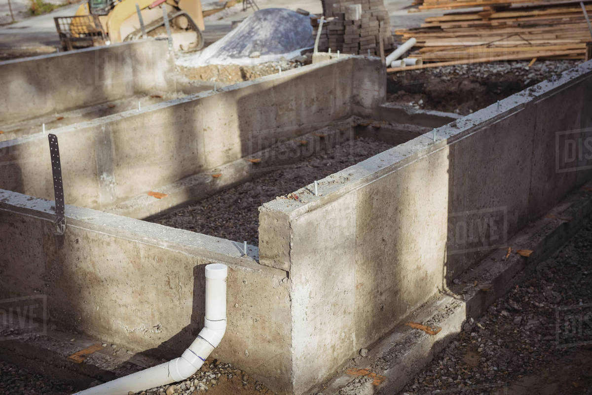 Concrete foundation and drainage pipe at construction site stock photo