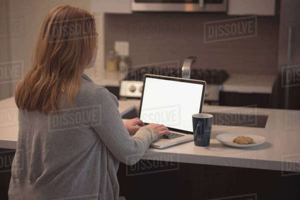 Rear view of woman using laptop at kitchen island at home Royalty-free stock photo