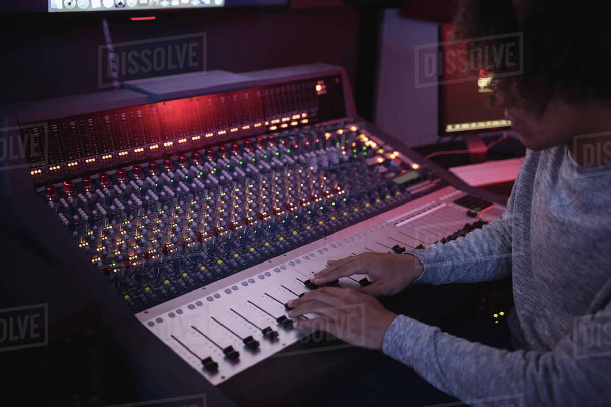 Male audio engineer using sound mixer in recording studio stock photo