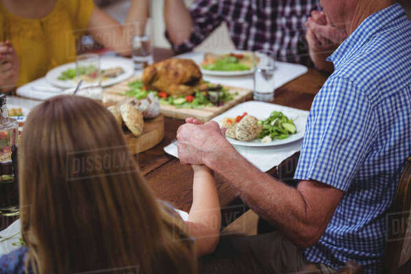 Family holding hands while praying at dining table Royalty-free stock photo