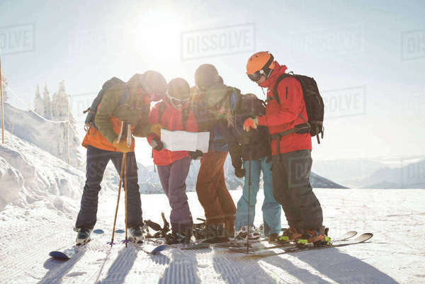 Group of skiers looking at map in snowy alps during winter Royalty-free stock photo