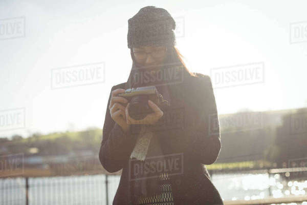 Woman looking at photos on digital camera in park on a sunny day Royalty-free stock photo