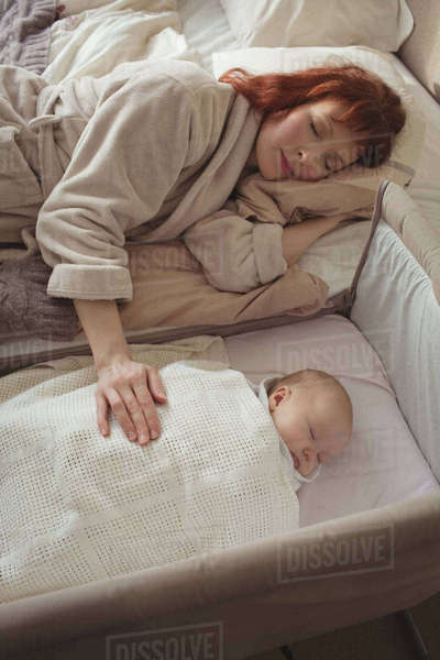 High angle view of mother and baby sleeping in bedroom  Royalty-free stock photo