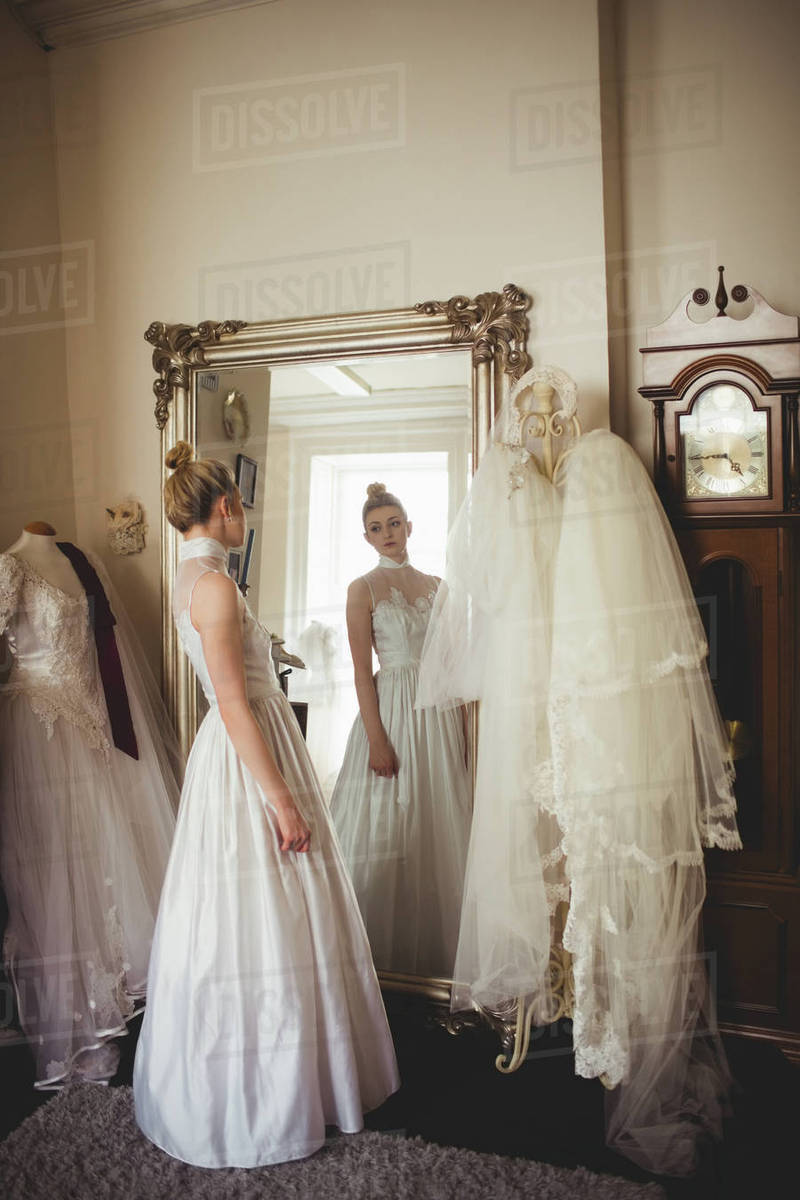 d109333de29 Young bride in a white dress looking into mirror in a boutique ...