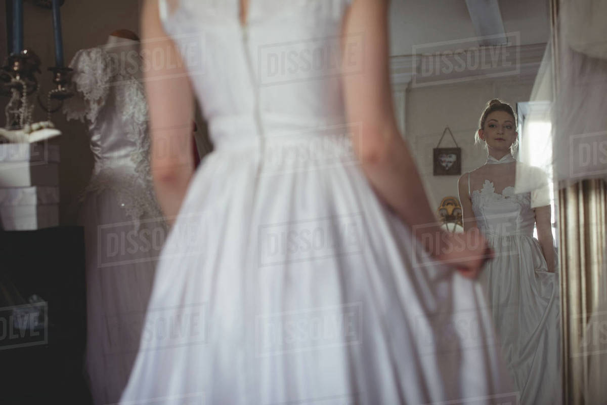 7c328883c73 Young bride in a white dress looking into mirror at boutique - Stock ...
