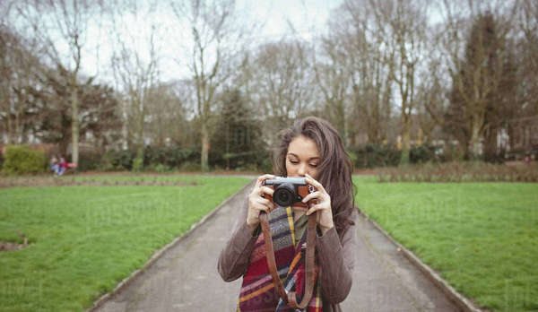 Woman taking photo from digital camera in park Royalty-free stock photo
