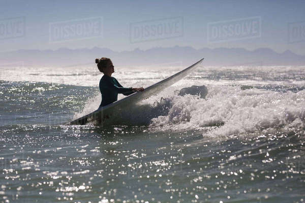 Female surfer surfing in the sea with surfboard on a sunny day Royalty-free stock photo