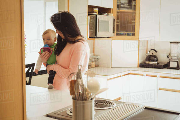 Mother feeding her little baby girl from the milk bottle in kitchen at home Royalty-free stock photo