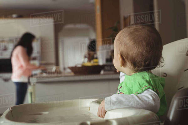 Close-up of baby girl looking at a mother working at kitchen Royalty-free stock photo