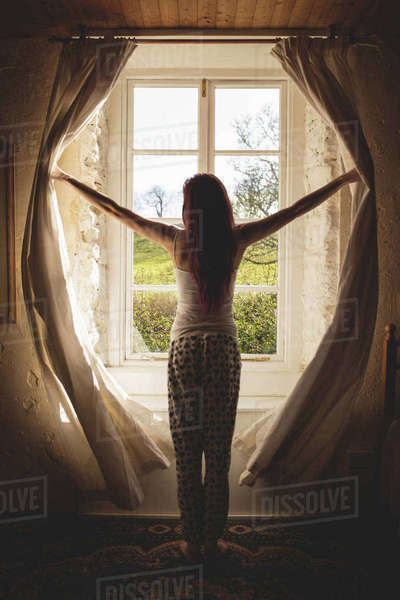 Rear view of woman opening her bedroom curtains in the morning Royalty-free stock photo