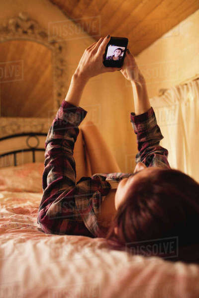 Woman lying on bed and taking a selfie on mobile phone in the bedroom Royalty-free stock photo