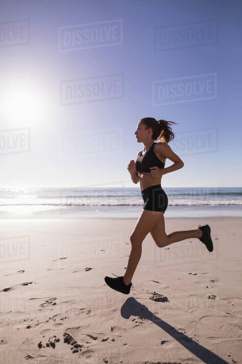 Fit Woman Jogging In The Beach At Dusk