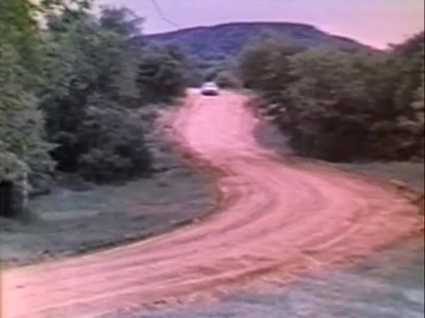 Lockdown shot of a car driving on a dirt road through forest with lots of dust Royalty-free stock video