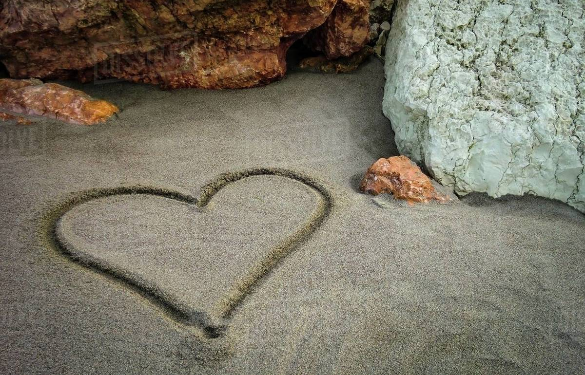 A heart drawn on the sand of the unspoiled beach: a gesture of sweet and poetic love for those who truly love Royalty-free stock photo