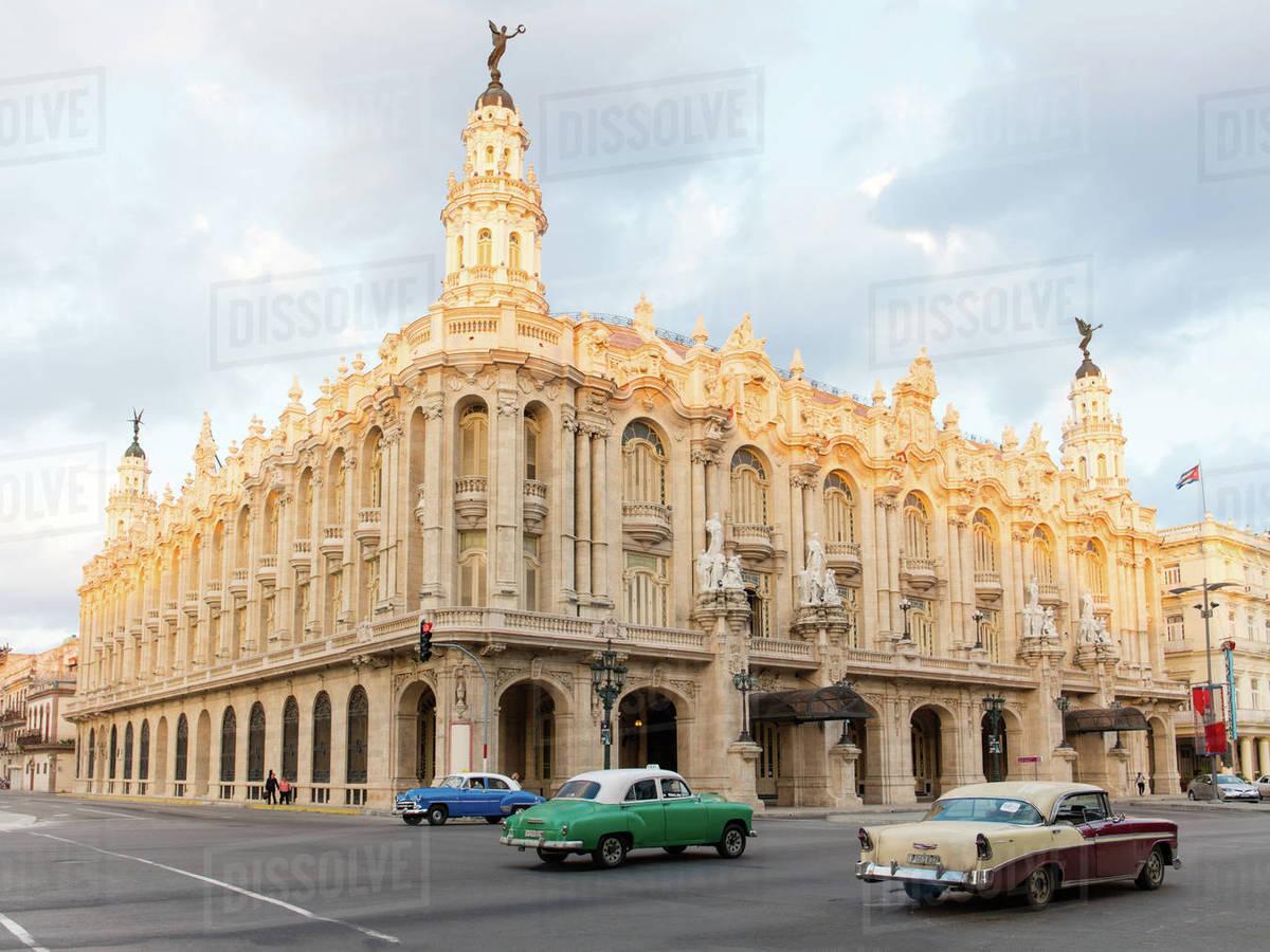 Old American cars drive past the Gran Teatro de La Habana in Havana, Cuba, West Indies, Caribbean, Central America Royalty-free stock photo