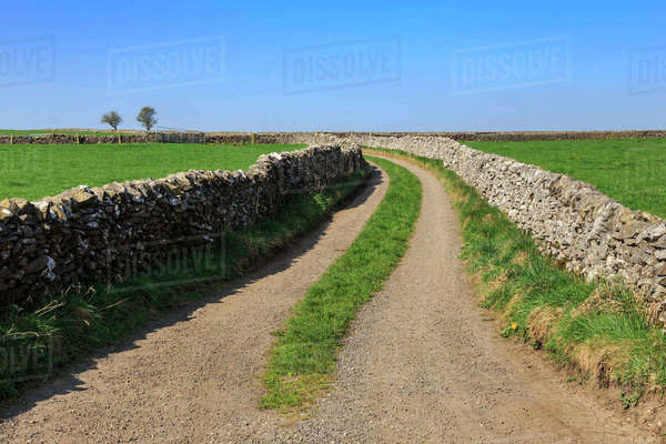 Track disappears into distance, between dry stone walls, a typical country scene, Peak District, Derbyshire, England, United Kingdom, Europe Royalty-free stock photo