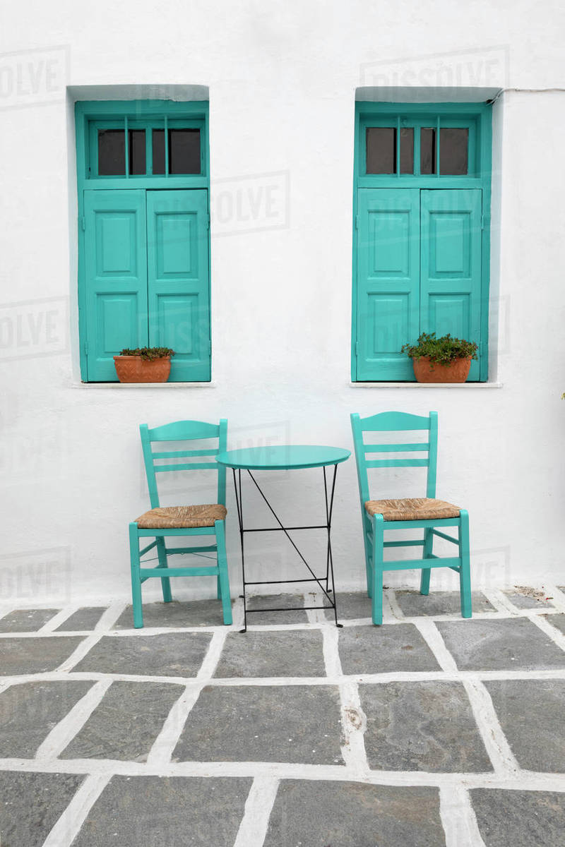 Typical Greek cafe table and chairs with shuttered windows, Pano Chora,  Serifos, Cyclades, Aegean Sea, Greek Islands, Greece stock photo