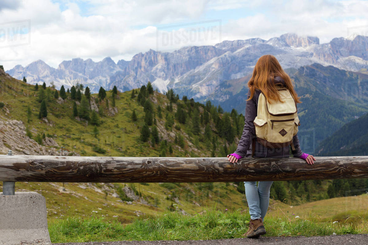 girl hiker sitting  and looking at the snowed mountains. Dolomites, Italy. Royalty-free stock photo