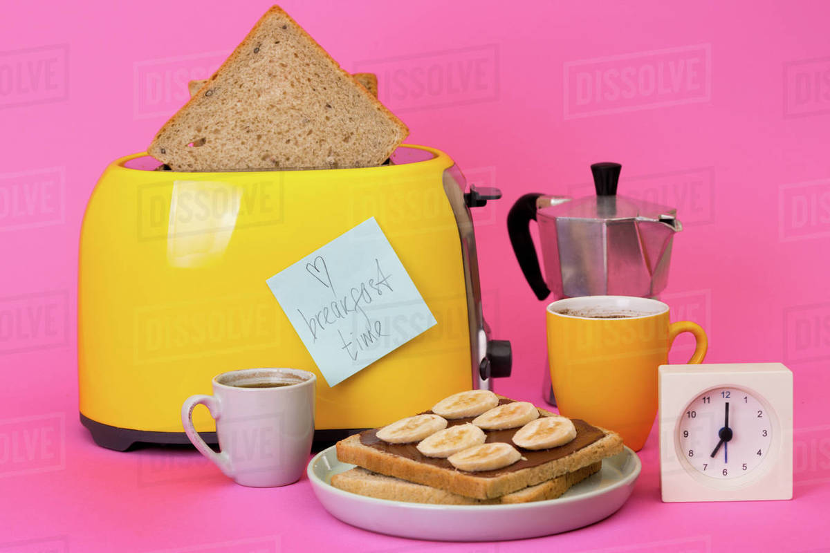 Bright, fun breakfast. yellow toaster and a cup of coffee on a pink background Royalty-free stock photo