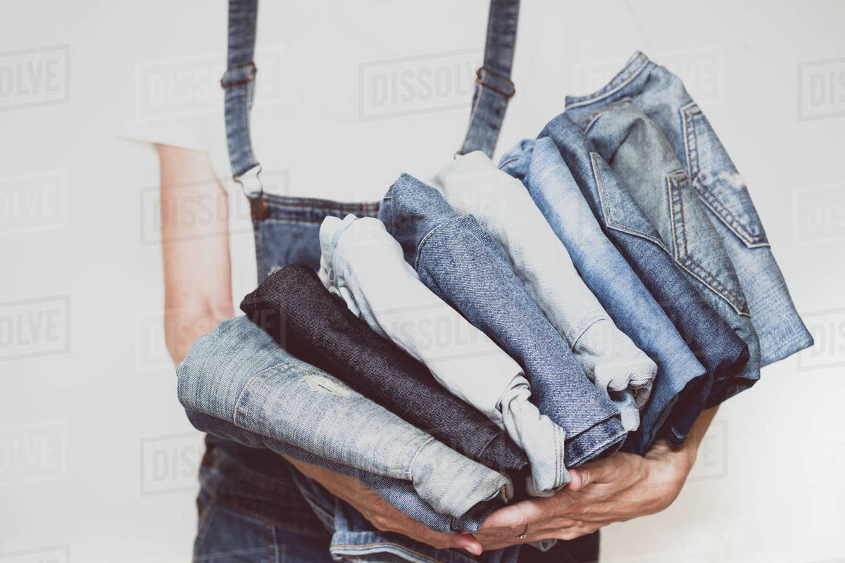 The girl holds a stack of jeans in her hands. cleaning in the closet. Royalty-free stock photo