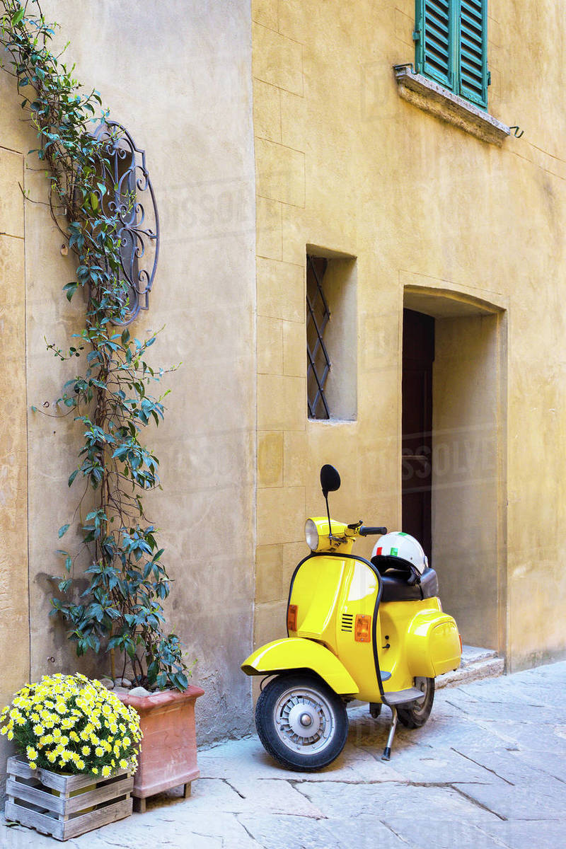 Scooter standing at the empty street of old italian town. Pienza, Tuscany, Italy Royalty-free stock photo