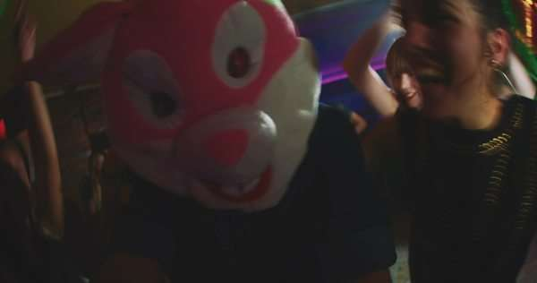 Group of friends at a party with one wearing a plush rabbit head Royalty-free stock video
