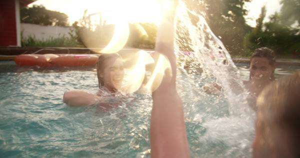 Backyard swimming pool on a late summer evening with girls splashing each other with water while play fighting, with colourful sun flare in slow motion Royalty-free stock video