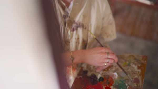Vintage themed image of a young woman artist  wearing a well worn old-fashioned artist's smock covered with paintwhile working with a fine brush on a canvas in her studio Royalty-free stock video