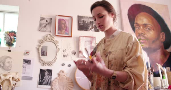 Young woman artist holding some paintbrushes in her creative studio wearing an old-fashioned artist's smock which is covered with paint marks Royalty-free stock video