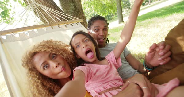Attractive mother and father spends quality time with their adorable daughter, taking wacky selfies and swinging around on a hammock outdoors in nature. Royalty-free stock video