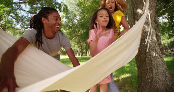 Attractive young mom and dad spends time with their children during the weekend outside in the sunny garden relaxing and bonding on a hammock. Royalty-free stock video